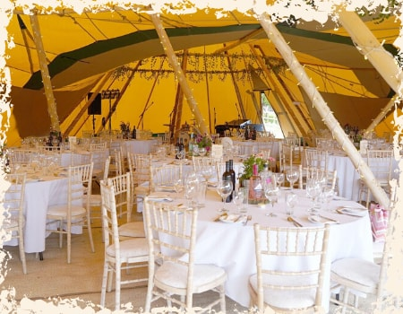 Tables laid inside tipi wedding venue Overgrown Acres