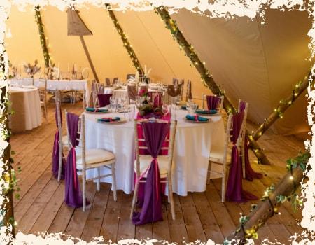 Tables laid inside tipi wedding venue Overgrown Acres